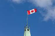 Canadian Flag flies on the top of the Peace Tower at the Parliament Buildings' Centre Block building in Ottawa, Ontario, Canada. The Peace Tower is 92.2 m (302 ft ) in height and was completed in 1927 after the original tower (Victoria Tower) burned down with the rest of the original Centre Block building in 1916.