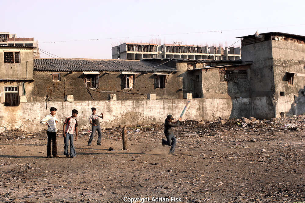 Boys play cricket. In the centre of Dharavi is a large empty area that provides much joy for the youth of the slum. In the background a new tower block is being built, Dharavi occupies prime real estate in Bombay and developers are exploiting this with questionable benefit to the slum dwellers.