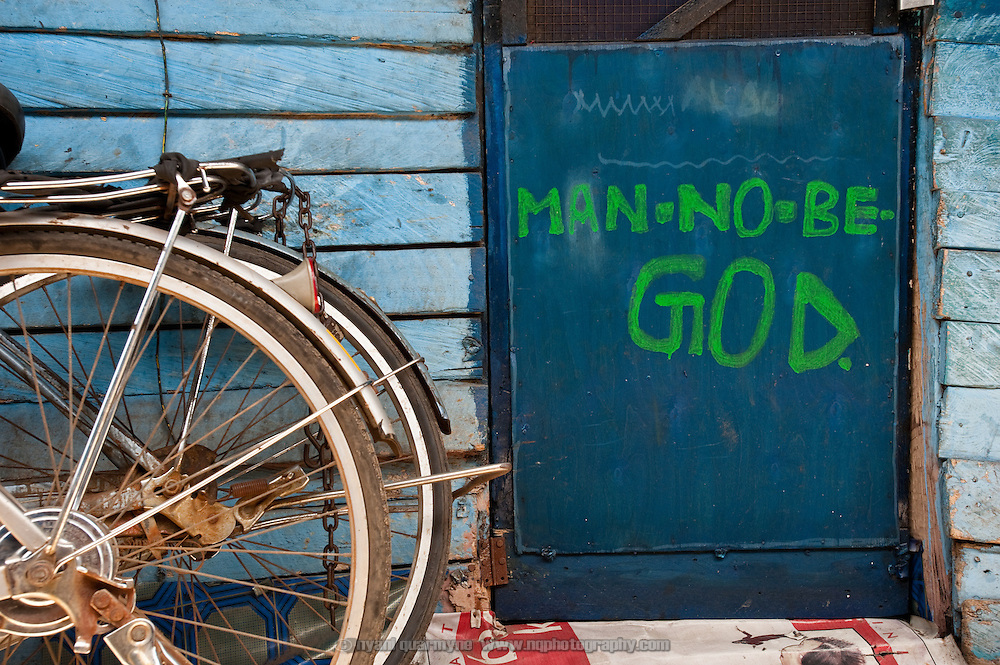 """Man No Be God"" is seen on the door of a one-room home in Old Fadama. Colloquially referred to as 'Sodom and Gomorrah, Old Fadama is located in Ghana's capital Accra and is home to some some 80,000 people."