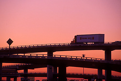 Shipping truck passing over an elevated freeway at sunset in Houston Texas