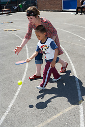 Boy taking part in sports day competition in school playground; with teacher helping,