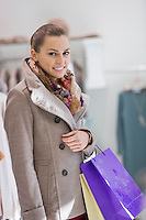Portrait of young woman with shopping bags in store