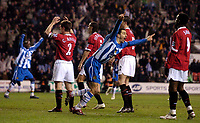 Photo: Jed Wee.<br /> Wigan Athletic v Manchester United. The Barclays Premiership. 06/03/2006.<br /> <br /> Wigan's Paul Scharner wheels away in celebration after scoring as the Manchester United players show their disappointment.