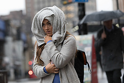 © Licensed to London News Pictures. 28/03/2018. London, UK. A woman covers her head with a scarf as she walks from Waterloo Station during rain and wet weather this morning. Photo credit: Vickie Flores/LNP