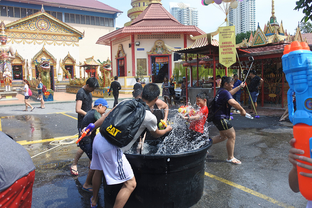People at the Songkran festival throwing water in buckets at each other from a alrge tank of water, water is frozen in motion0