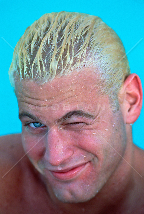 Wet bleach blond man in a swimming pool winking