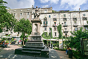 The Piazza Bellini with the statue of Vincenzo Bellini in Naples, southern Italy. The plaza features the palaces of Firrao-Bisingano, Castriota Scanderbeg, and the Principi di Conca and the subterranean ruins of the former western walls of the Ancient Greek city of Neapolis.