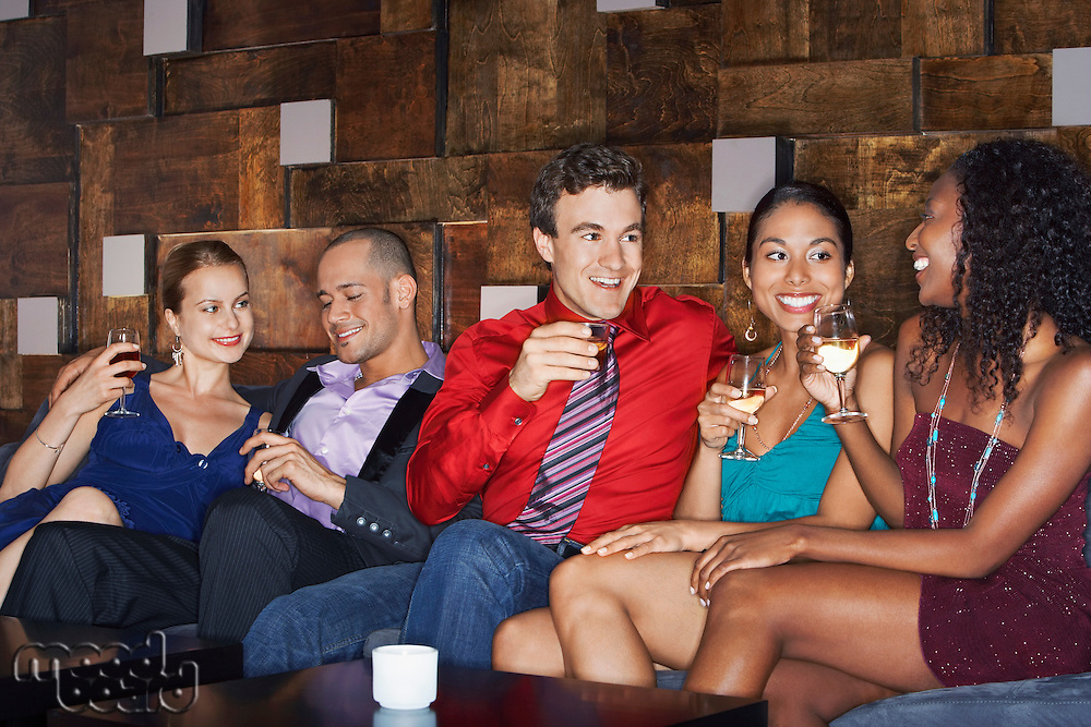 Friends talking and drinking while sitting in bar