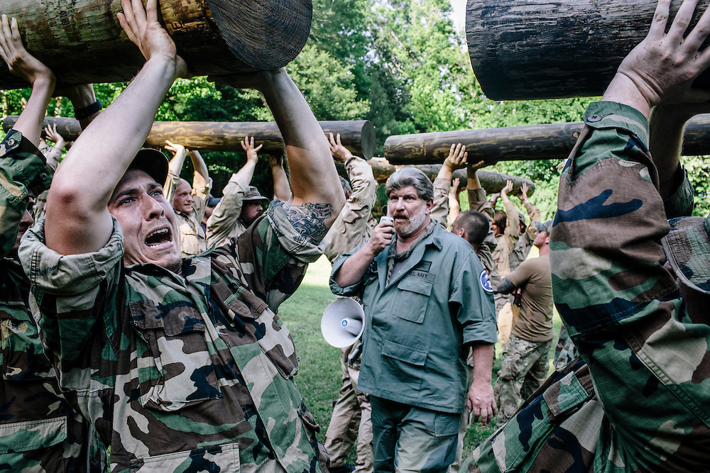 Don Shipley teases  participants as they try to keep giant logs above their heads in what is known as 'log PT.' The winners would get to rest as the rest would have to  go through the competition again.