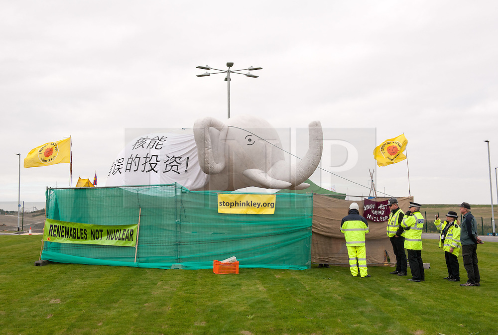 """© Licensed to London News Pictures. 19/10/2015. Hinkley Point, Somerset, UK.  Officials deliver papers to an Anti-nuclear protest by the group """"Osborne's Folly"""" (after the Chancellor George Osborne), protesting against the proposed new nuclear power station Hinkley C and against Chinese investment in the project.  The papers ask the protesters to leave by 5pm or legal proceedings will begin to regain possession of the land. The group has occupied a roundabout near the site and erected an inflatable white elephant with a banner written in Chinese and say they want to send a message to the visiting Chinese President Xi Jinping that EDF's Hinkley C would be """"a bad investment"""" for the Chinese state. They say that the stalled project has become """"Osborne's Energy Folly"""" and should now be abandoned.  Theo Simon, one of the campaigners said: """"""""Ironically, the Chinese are leading the world in renewable energy investment in their own country, where there is also a growing anti-nuclear movement"""". Photo credit : Simon Chapman/LNP"""