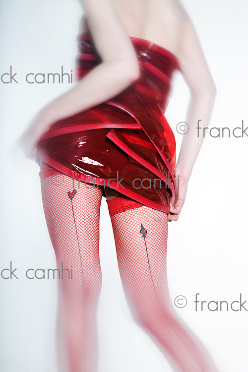 Funny & sexy expressive redhead girl wearing a palstic coat and dress on isolated background from back