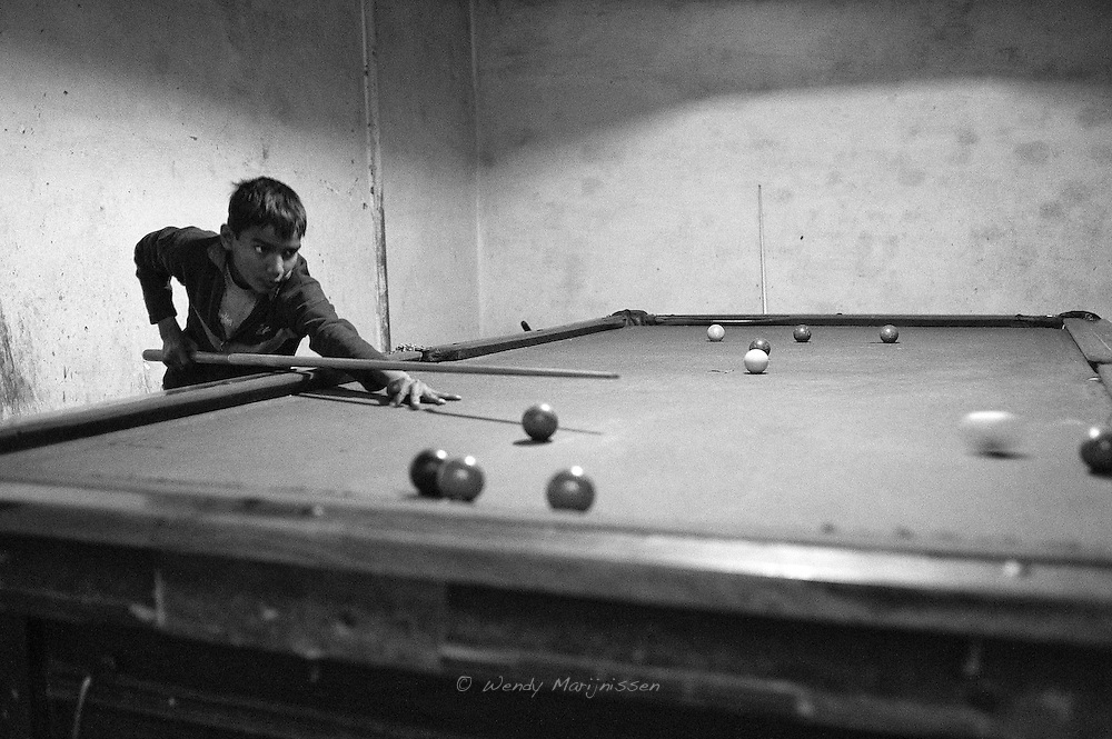 A boy is playing pool in a make shift entertainment hall inside the French colony slum.