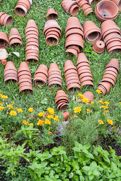 Red clay pots lay still stacked on the green lawn with yellow flowers