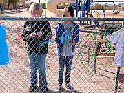 tucsonshooting - 10 JANUARY 2011 - ORO VALLEY, AZ: School mates of Christina Green tie ribbons to the memorial for their deceased school mate at Mesa Verde Elementary School in Oro Valley. Christina Green was a student at the school, and was one of the people murdered Saturday in the mass shooting in Tucson.  ARIZONA REPUBLIC PHOTO BY JACK KURTZ..Gabrielle Giffords shooting