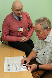 Volunteer with patient using illuminated magnifier to look at Harsant vision chart in consulting room in eye clinic at QMC hospital, Nottingham.