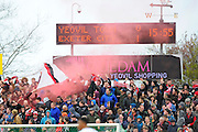 Exeter fans celebrate their teams opening goal by letting off a red smoke bomb during the Sky Bet League 2 match between Yeovil Town and Exeter City at Huish Park, Yeovil, England on 9 April 2016. Photo by Graham Hunt.