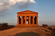 View from the front of the Temple of Concord, 5th century BC, Agrigento, Sicily, Italy,  pictured on September 11, 2009, in the warm evening light. Well preserved owing to its 6th century AD conversion to a church, the Temple of Concord is a typical example of optical correction whose tapering columns create the illusion of a perfectly aligned building. Its frieze consists of alternating triglyphs and metopes, and the pediment is undecorated. The Valley of the Temples is a UNESCO World Heritage Site. Picture by Manuel Cohen.