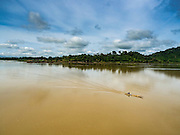 20 JUNE 2016 - DON KHONE, CHAMPASAK, LAOS: A man in motorized canoe approaches the south end of Don Khone Island. Don Khone Island, one of the larger islands in the 4,000 Islands chain on the Mekong River in southern Laos. The island has become a backpacker hot spot, there are lots of guest houses and small restaurants on the north end of the island.     PHOTO BY JACK KURTZ
