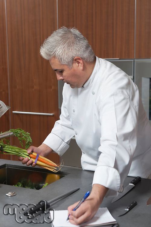 Mid- adult chef holding carrots and writing in notebook