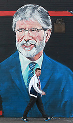 A young man walks past a new mural of Gerry Adams which appeared on the Falls Road, west Belfast, Northern Ireland, on Friday, 2nd May 2014. Picture by i-Images