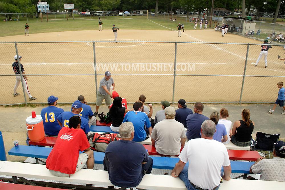 Middletown, N.Y. - Spectators in the bleachers watch two men's teams play in the Neal B. Turfler softball tournament on Aug. 19, 2006. ©Tom Bushey
