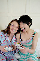 Two female friends playing video game