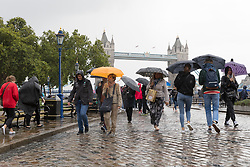 © Licensed to London News Pictures. 10/08/2018. London, UK.  Tourists are caught in a heavy rain shower and wet weather near the Tower Bridge at lunchtime today.  Photo credit: Vickie Flores/LNP