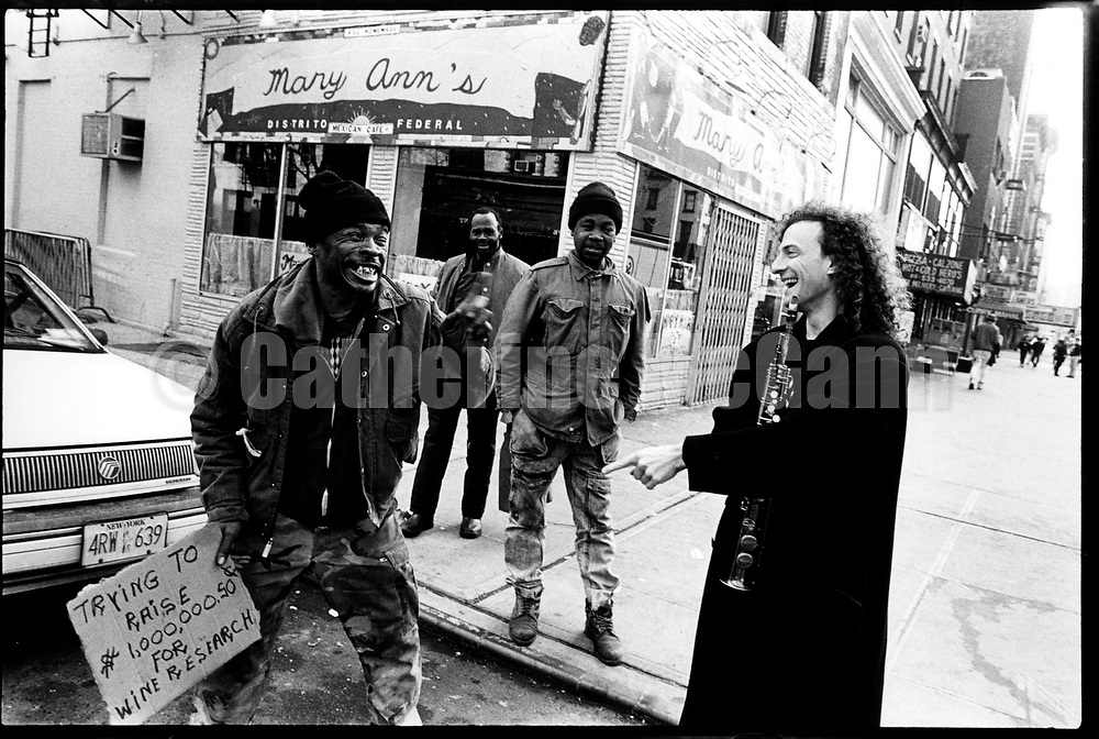 NEW YORK - MARCH 1993:  American musician Kenny G, right,  holds his clarinet while laughing with a street person who holds a sign saying he is trying to raise money for wine research in the East Village in March 1993 in New York City, New York (Photo by Catherine McGann).Copyright 2010 Catherine McGann