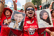 19 MAY 2013 - BANGKOK, THAILAND:   A Thai Red Shirt holds up photos of ousted Prime Minister Thaksin Shinawatra and his sister, current Primie Minister Yingluck Shinawatra during a Red Shirt rally in Ratchaprasong Intersection honoring Red Shirts killed by the Thai army in 2010. More than 85 people, most of them civilians, were killed during the Thai army crackdown against the Red Shirt protesters in April and May 2010. The Red Shirts were protesting against the government of Abhisit Vejjajiva, a member of the opposition who became Prime Minister after Thai courts ruled the Red Shirt supported government was unconstitutional. The protests rocked Bangkok from March 2010 until May 19, 2010 when Thai troops swept through the protest areas arresting hundreds.  PHOTO BY JACK KURTZ