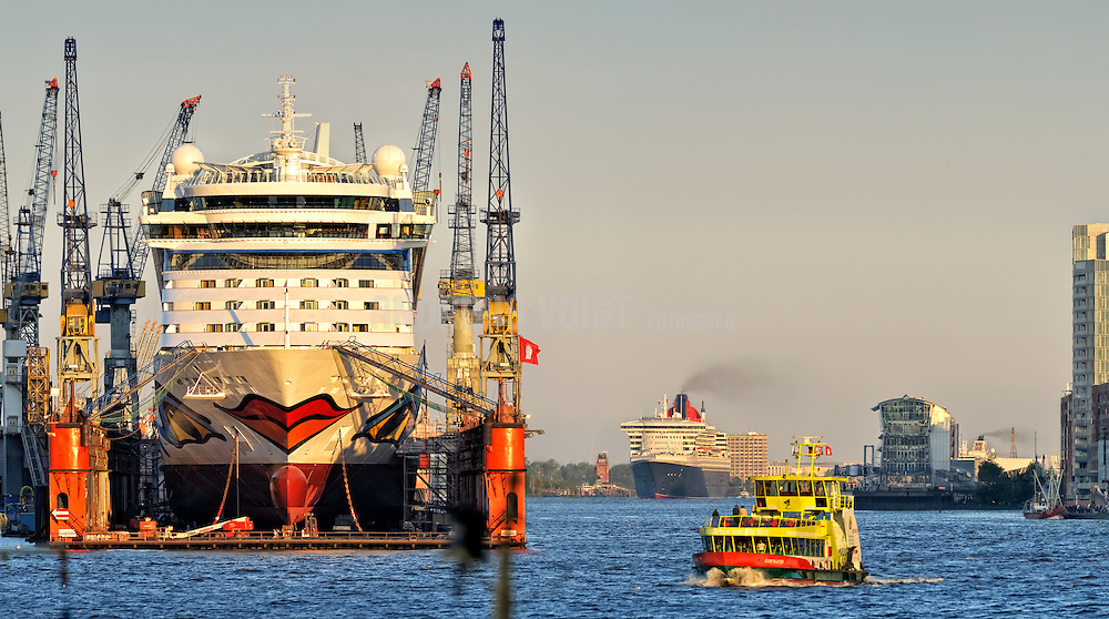 Die Queen Marry II läuft am Sonntagmorgen des Hafengeburtstags in Hamburg ein. Im Trockendock von Blohm & Voss liegt die Aidablue, eine Hafenfähre kreuzt.