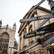 Signposts point to some of the major tourist sights in bath, Somerset, with the tower of the West Front of Bath Abbey in the background at left.