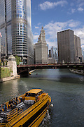 A water taxi travels the Chicago River by State Street in Chicago, IL.