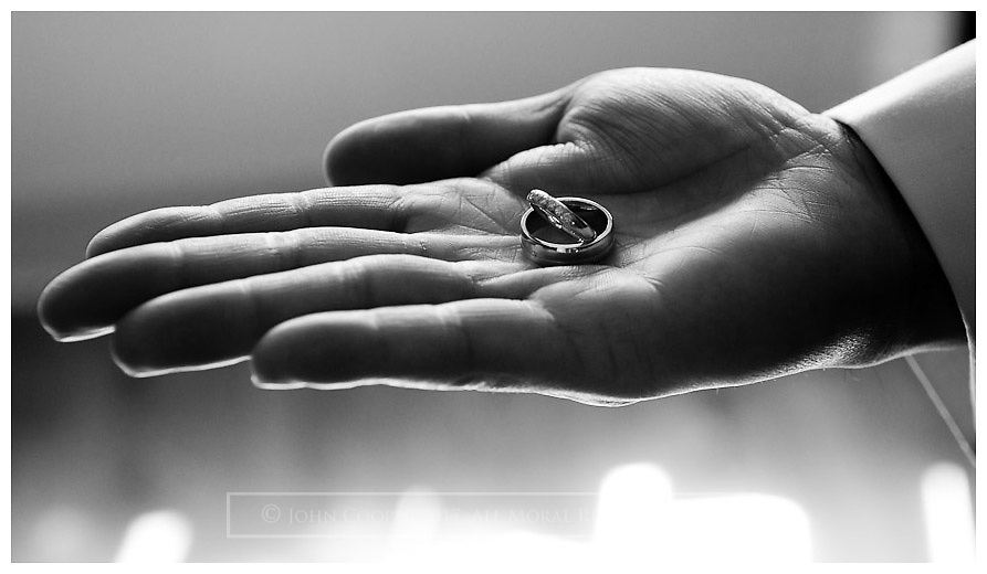 Close up of best man's hand holding wedding rings.