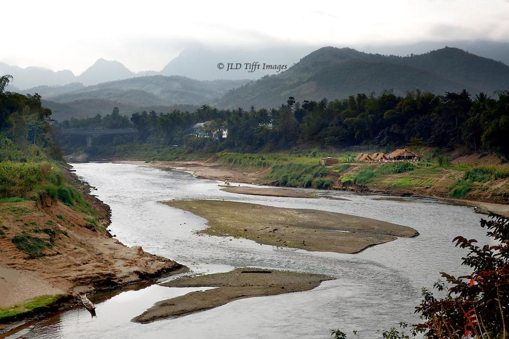 Mekong River near Luang Prabang, Laos.  Small row boats and a farm visible along its banks.
