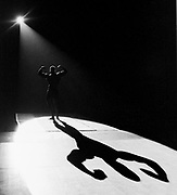 A spotlight casts the shadow of a body building competitor's form during a regional competition in Tulsa, OK.