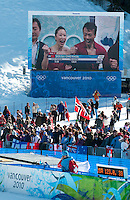 A crowd of fans watches the big screen tv broadcast for skating during a break at the ski jump medals round at the 2010 Olympic Winter Games in Whistler, BC Canada.