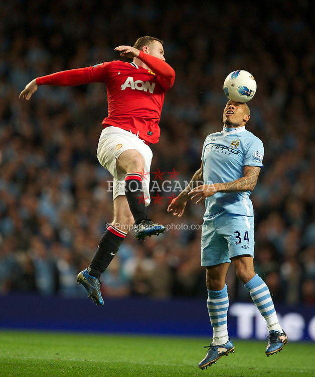 MANCHESTER, ENGLAND - Monday, April 30, 2012: Manchester City's Nigel de Jong in action against Manchester United's Wayne Rooney during the Premiership match at the City of Manchester Stadium. (Pic by David Rawcliffe/Propaganda)