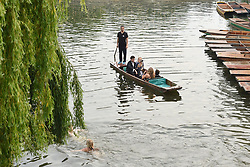 Students enjoy a punt ride along the river Cam after attending a May Ball at Cambridge University which is the traditional celebration to mark the end of the academic year.