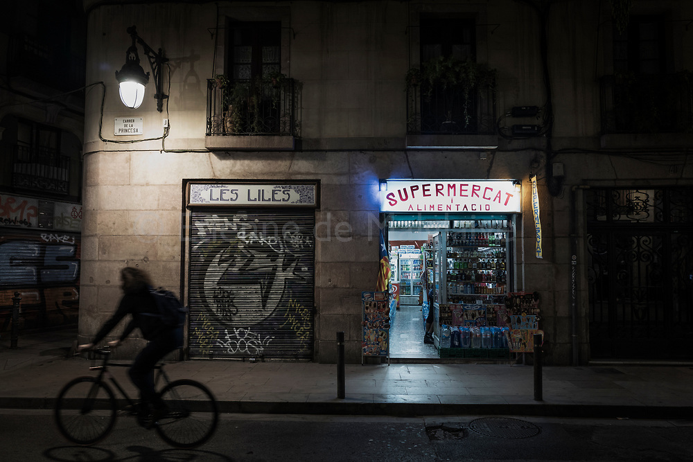 A biker rides next to a convenience store displaying an independent Catalonia flag in El Born district. Four days earlier, Catalan parliament voted Catalonia independence and Spanish government retaliated by imposing direct rules, dissolving parliament, firing top officials. November 01, 2017 in Barcelona, Spain.