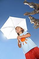 Boy (7-9) holding beach umbrella view from below