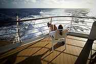 A young woman looks out on the Atlantic Ocean from the deck of a cruise ship.