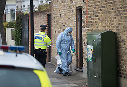 © Licensed to London News Pictures. 21/09/2017. London, UK. A police forensics officer enters a house where police and the fire brigade attended and found a burnt body in the garden in Southfields, south London A 40-year-old man and a 34-year-old woman were arrested at the scene on Wednesday, 20 September on suspicion of murder. Photo credit: Peter Macdiarmid/LNP