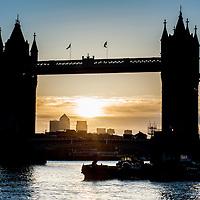 The sun rises behind Tower Bridge in London