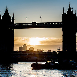 The sun rises behind Tower Bridge in London