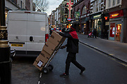 A courier pushes a trolley stacked with boxes across Long Acre, on 12th December 2017, in London England.
