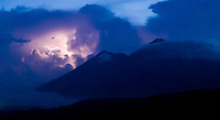 Aerial drone image of lightning behind Volcán de Fuego and Volcán de Acatenango (left and right peaks in the distance) at sunset, seen from above Antigua Guatemala, on Tuesday, Sept. 18, 2018. While Acatenango is dormant, Fuego is highly active and an eruption on June 3, 2018 caused heavy loss of life and property.