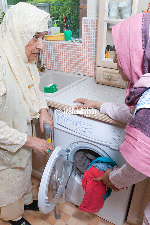 Young female carer helping an older woman fill her washing machine,