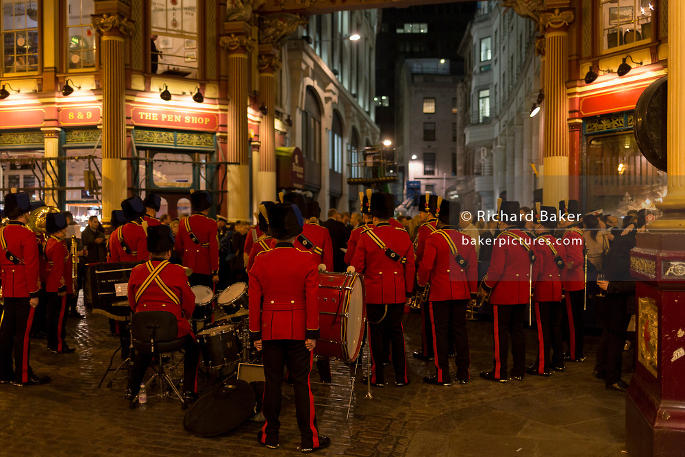 Wearing red uniforms, a military band takes a breather between musical evening to help with the Poppy Appeal, in Leadenhall Market in the Square Mile, the heart of the capital's historical financial district, on 2nd October 2017, in the City of London, England.