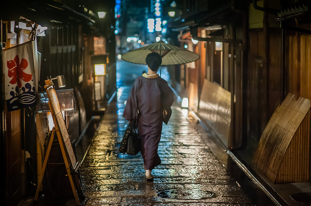 Woman in kimono under umbrella in Kyoto