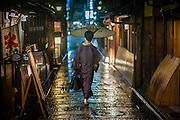 Woman in kimono under umbrella in Kyoto